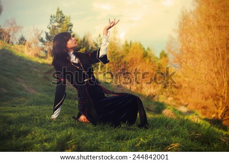 A beautiful young woman with dark hair and a historical dress posing on a meadow in open lanscape with a gesture of connection between heavenly and earth worlds - stock photo