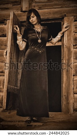 A beautiful young woman with dark hair in a black velvet historical dress is standing at the door of a forest log cottage, vintage sepia version