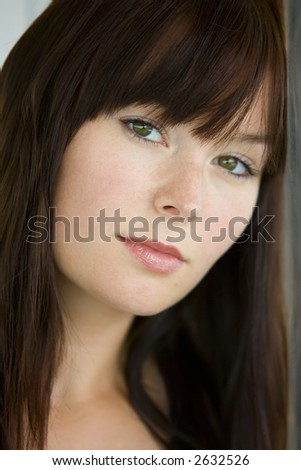 A beautiful young woman with green eyes stares wistfully into the camera