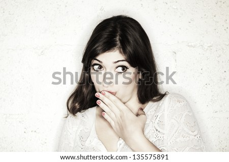 A beautiful young woman with her eyes wide open glancing sideways, with her hand covering her mouth.Looks like she is feeling shy towards something, or maybe guilty. Either way, she is very cute. - stock photo
