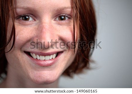 A beautiful young woman with short wet hair smiling and looking at the camera.