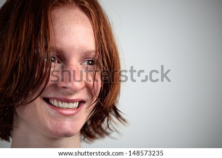 A beautiful young woman with short wet hair smiling and looking sideways.