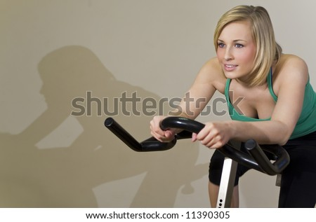 A beautiful young woman working out on an exercise bike at the gym with her shadow on the wall next to her like a competitor always in the lead