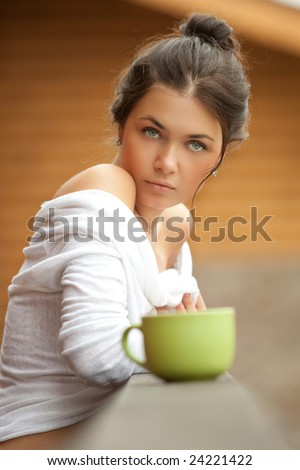A  beautiful young women in white blouse drinks tea from a green cup - stock photo