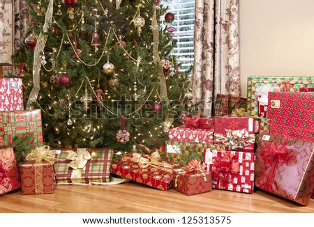 A beautifully decorated Christmas tree with lots of pretty wrapped holiday gifts