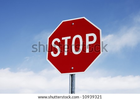 A beautifully lit stop sign against a light blue sky with scattered clouds.