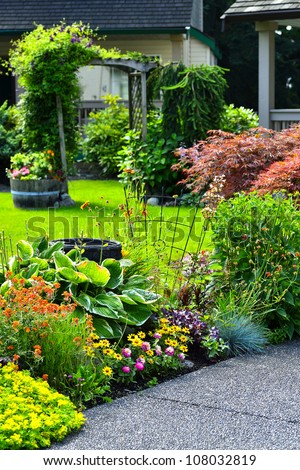A beautifully manicured yard with a garden full of annuals and perennials. - stock photo