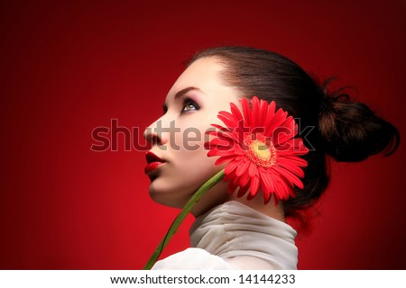 a beauty brunette with red flower looking up - stock photo