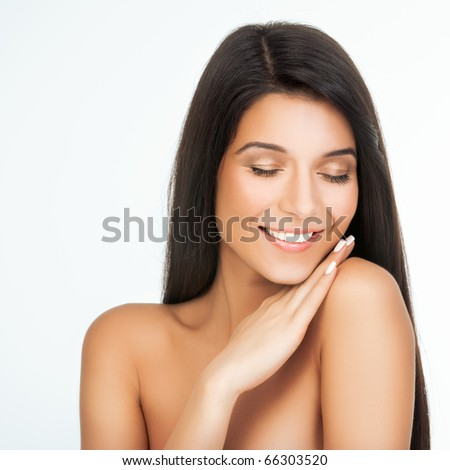 a beauty portrait of a young woman, shot on white background, with one hand on her shoulder and her face touching the hand. she is smiling and her eyes are closed.