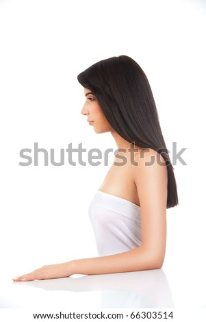 a beauty profile portrait of a young woman, shot on white background. she has one hand on a white table. - stock photo