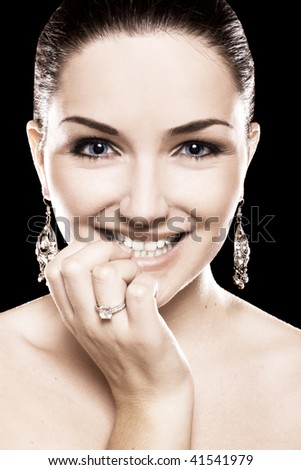 A beauty shot of a pretty young woman wearing a diamond ring and earrings in front of a dark background. - stock photo