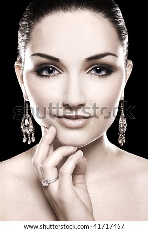 A beauty shot of a pretty young woman wearing a diamond ring and earrings in front of a dark background.