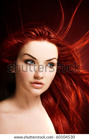 A beauty shot of a young blue eyed woman with her red hair flowing in the wind.