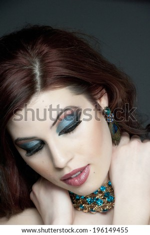 A beauty shot of a young girl model posing on a dark background in a studio.