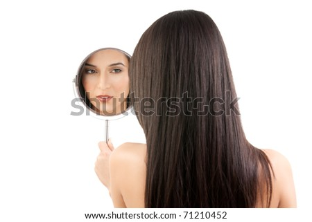 a beauty studio picture of a young woman looking in a mirror, while her back is turned to the camera. the mirror held over her left shoulder reflects her face. - stock photo