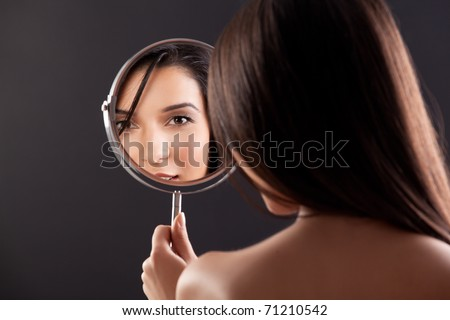 a beauty studio picture of a young woman looking in a mirror, while her back is turned to the camera. the mirror held over her left shoulder reflects her smiling face. - stock photo