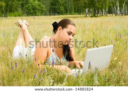 a beauty woman with laptop on the grass