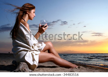 a beautyful  young woman drinking wine on the beach - stock photo