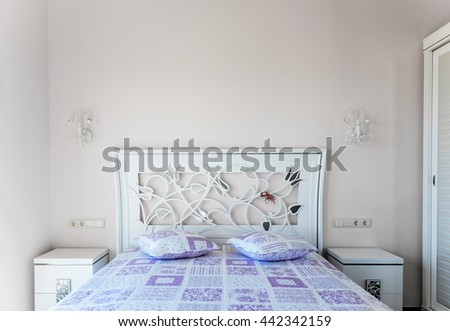 A bed in a bedroom. HeadBoard and purple cushions. Two bedside tables. Switches and Sockets. - stock photo
