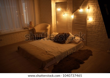 A bed in a rark room with a lights on a wall