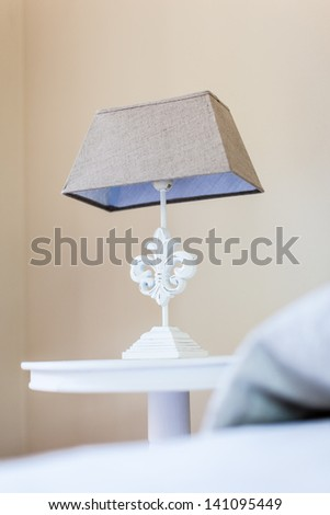 a bed side table with a classical style bed lamp on it - stock photo