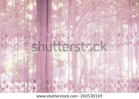 A bedroom windows dressed with striped curtain that lace drapery pattern with flower shape in an expensive luxury new home with the greens of the garden view. - stock photo