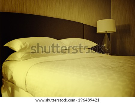 A bedroom with a lamp and fully made bed. - stock photo