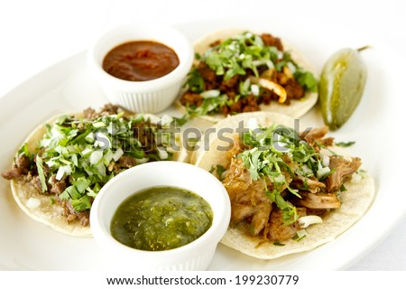 A beef, carnitas, and chicken taco with salsas. - stock photo