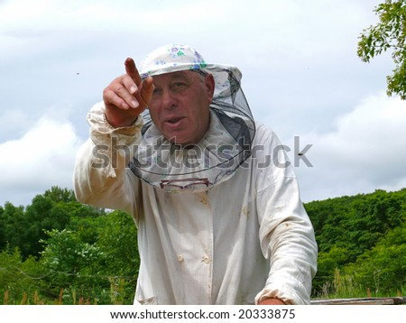 A beekeeper in veil at apiary. - stock photo