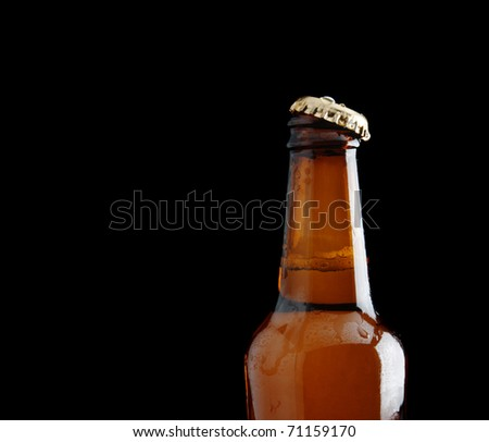 A beer bottle isolated on black background, with copy space - stock photo