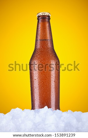 A beer bottle sitting on ice over a yellow background.