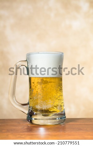 A beer mug freshly filled with cold, crisp beer with a nice foam head. - stock photo