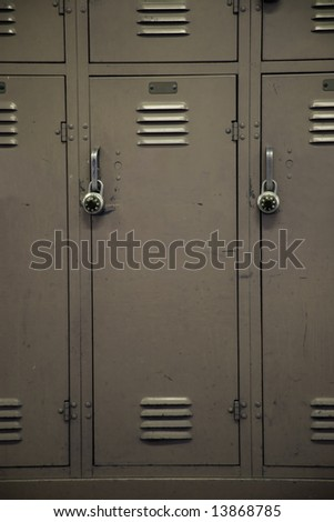 A beige colored school locker, typical of a high school. - stock photo