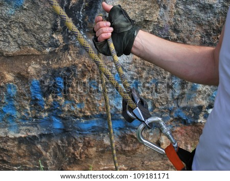 A belayer's hand holding the rope - stock photo