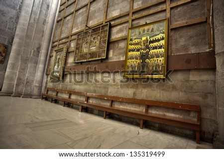 A bench and Christian classic art at the Basilica in the Church of the Holy Sepulchre in the old city of Jerusalem, Israel. - stock photo