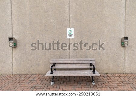 A bench flanked by two ash bins with a designated smoking area sign above. - stock photo