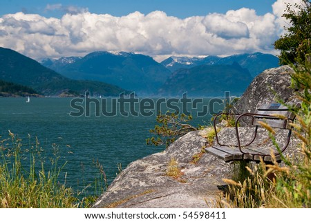 A bench on a rock in Whytecliff park. West Vancouver, Canada. Shallow depth of field. Focus on the closest subjects. - stock photo