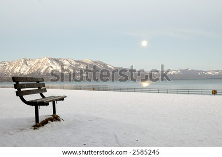 A bench on moonlit Regan beach at Lake Tahoe, California. The moon shines in the sky, lighting Sierra Nevada mountains. White balance adjusted to give the shot a daylight appearance.