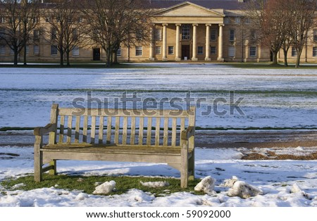 A bench on the lawn in Downing College Cambridge University - stock photo