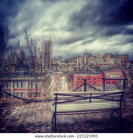 A bench overlooking a city of buildings and a stormy looking sky. - stock photo