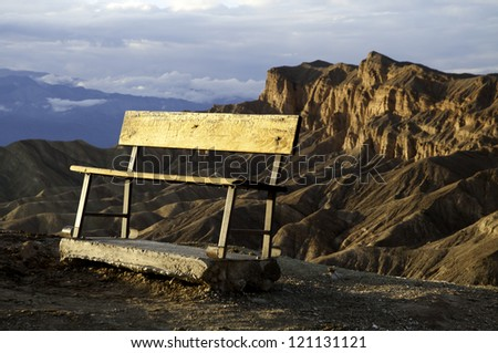 A bench overlooking a mountain vista in Death Valley National Park. - stock photo