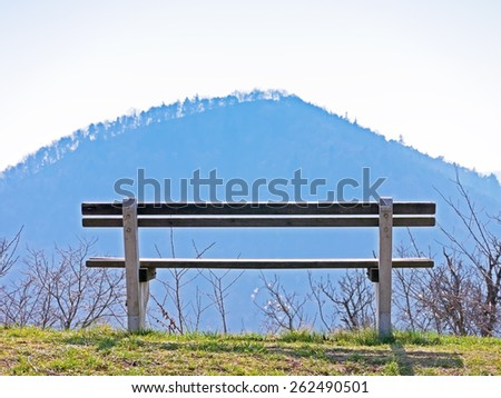 A bench with a view over a mountain.  - stock photo