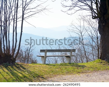 A bench with a view over mountains. - stock photo