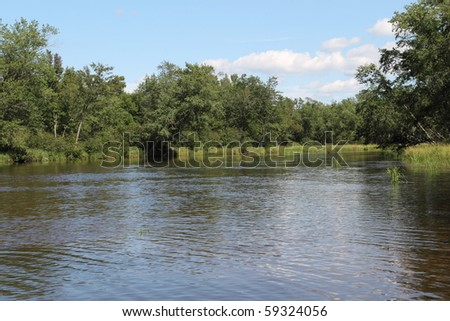 A bend in the Wisconsin River north of Rhinelander.  Beautiful summer image of green shoreline. - stock photo