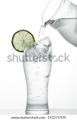 A beverage being poured over a tall glass of ice. - stock photo
