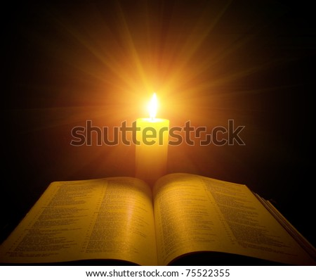 A bible open on a table next to a candle - stock photo