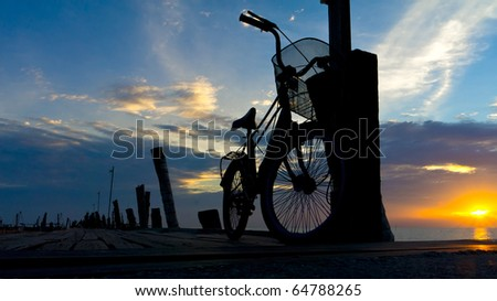 a bicycle on the edge of the jetty at sunset - stock photo