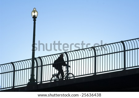 a bicycle rider travels across a bridge behind a fence - stock photo