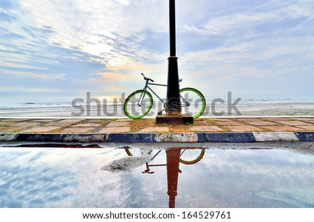 A bicycle with reflection near the beach in the morning - stock photo
