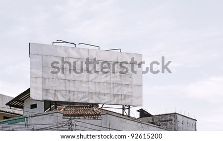 A big blank metallic advertisement billboard on the rooftop of an old building against a clear blue sky, with space for text.